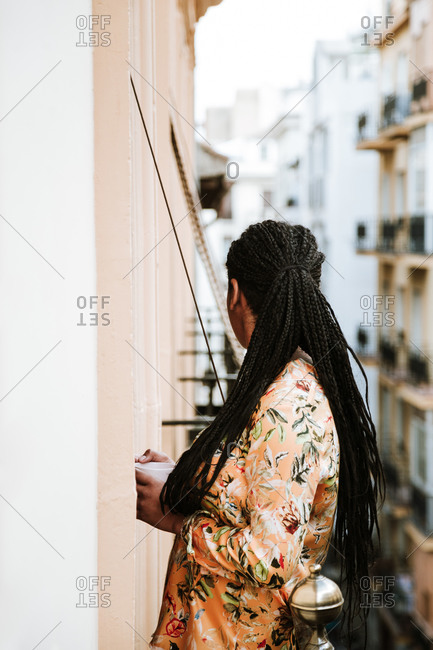 Young woman with cup of coffee standing on balcony