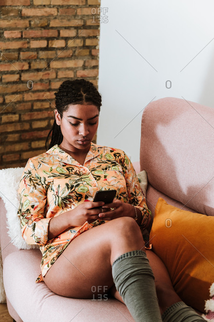 Modern African American female in casual wear sitting on comfortable sofa and browsing smartphone while resting in cozy living room with loft interior
