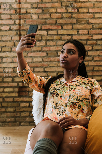 Serious young African American female in casual outfit taking selfie with smartphone while sitting on chair against brick wall in modern apartment
