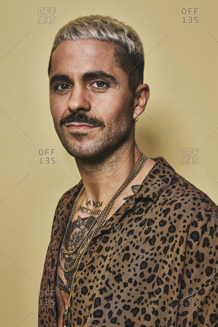Portrait of cheerful fashionable male model with tattoos wearing trendy leopard shirt standing against beige background and looking at camera