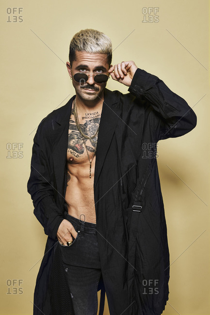 Brutal muscular sexy fit male with tattooed torso wearing black coat and trendy ripped jeans with stylish sunglasses and accessories standing against beige background looking at camera