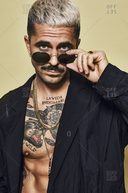 Portrait of brutal muscular sexy fit male with tattooed torso wearing black coat and stylish sunglasses and accessories standing against beige background looking at camera