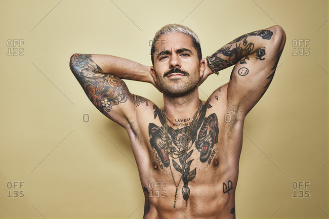 Handsome sexy muscular male with various tattoos on naked torso and arms looking at camera while standing against beige background