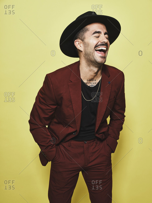 Laughing adult ethnic male in trendy vinous suit and hat with closed eyes standing against yellow background