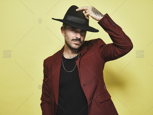 Handsome bearded well dressed male in trendy vinous suit and hat looking at camera against yellow background