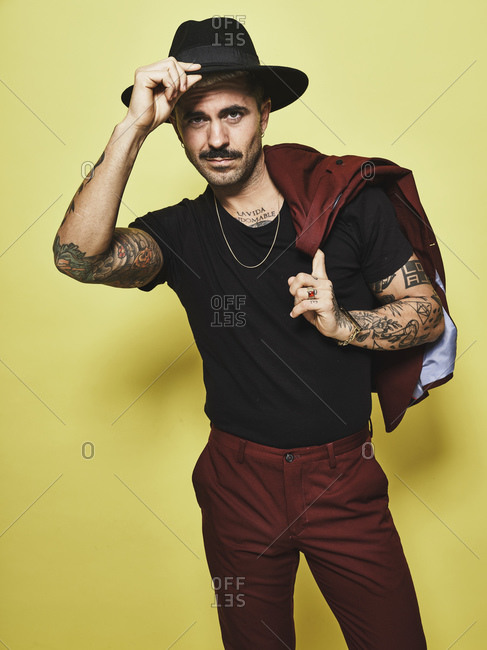 Handsome well dressed male with mustache in trendy hat and vinous suit holding suit coat over the shoulder looking at camera while standing against yellow background