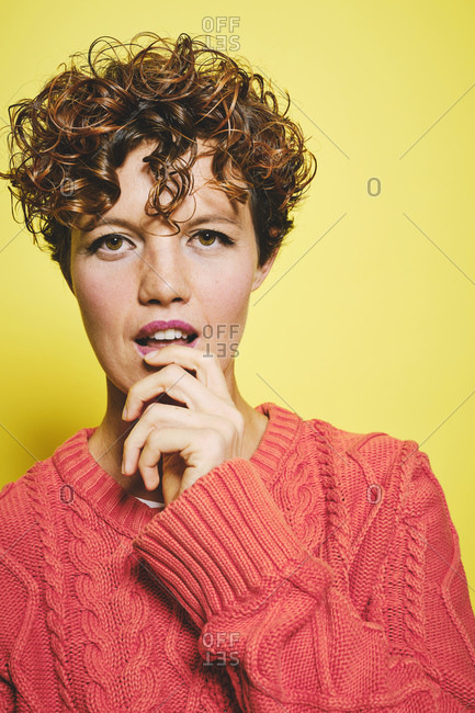 Amazed female with curly hair wearing orange knitted sweater with hand on mouth looking at camera while standing against yellow background