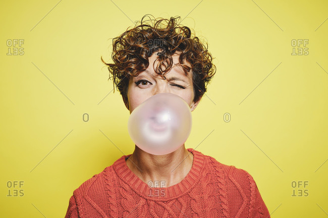 Young curly haired female in orange sweater blowing bubble gum and blinking looking to the camera while standing against yellow background