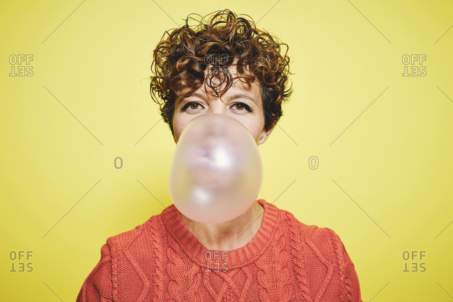 Young curly haired female in orange sweater blowing bubble gum looking to the camera while standing against yellow background