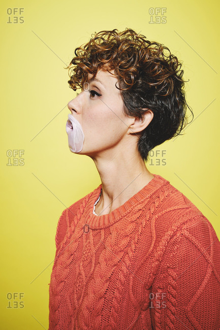 Side view of young pretty curly haired female in orange sweater trying to blow a bubble gum while standing looking away against yellow background