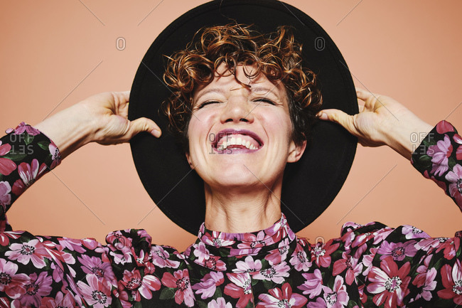 Optimistic young beautiful female model with curly hair wearing stylish black hat and colorful blouse with closed eyes smiling while standing against orange background