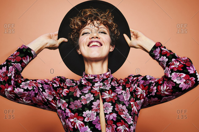 Optimistic young beautiful female model with curly hair wearing stylish black hat and colorful blouse looking at camera and smiling while standing against orange background