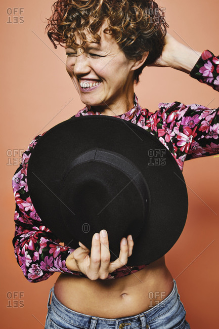 Fashionable happy female model holding a stylish black hat in colorful crop top with floral print standing against orange background with closed eyes