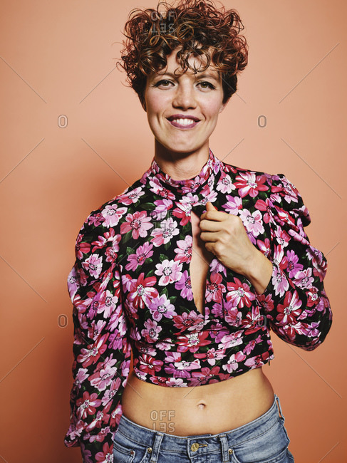 Fashionable happy pretty female model in stylish colorful crop top with floral print standing against pink background looking at camera