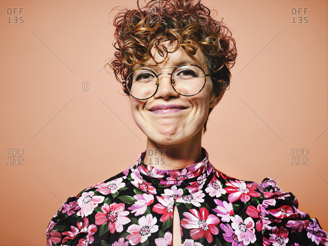 Happy young curly haired female in stylish floral blouse and trendy eyeglasses smiling and looking at camera against red background