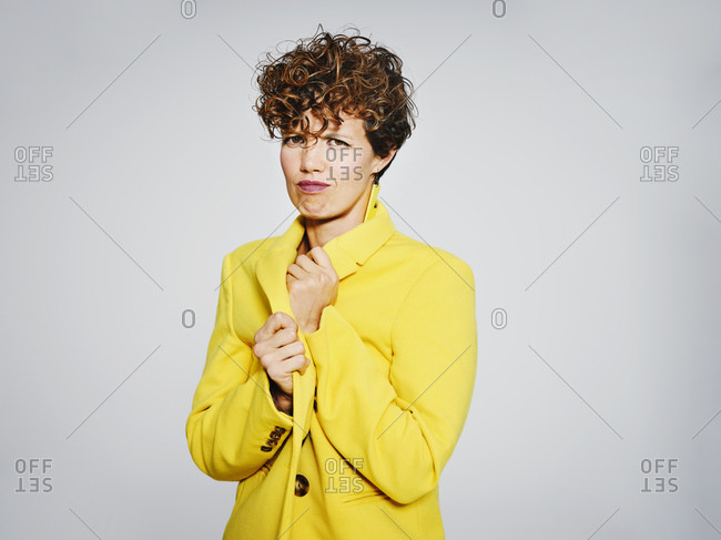 Portrait of cold woman with lightning earring adjusting stylish yellow coat against gray background looking at camera