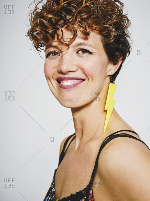 Portrait of cheerful woman with sequin top and lightning earring smiling to the camera while standing against gray background