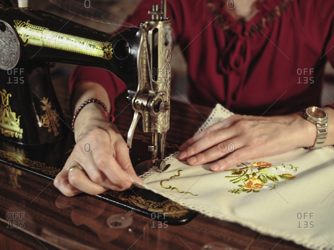 Senior lady in glasses using retro sewing machine to create linen napkin in cozy room at home