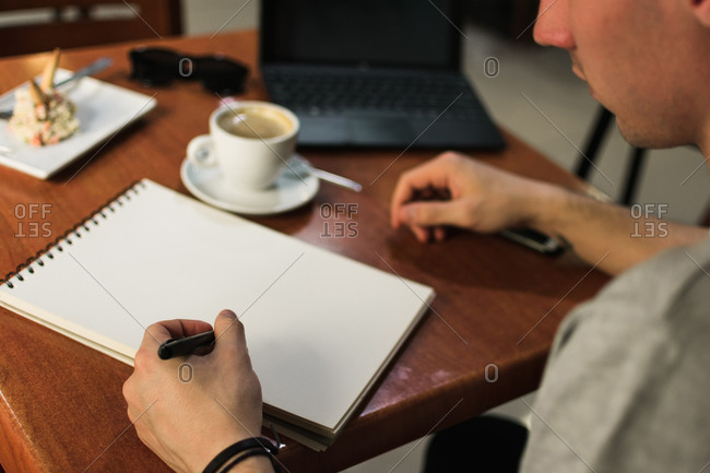 Crop freelancer drawing in notebook in cafe