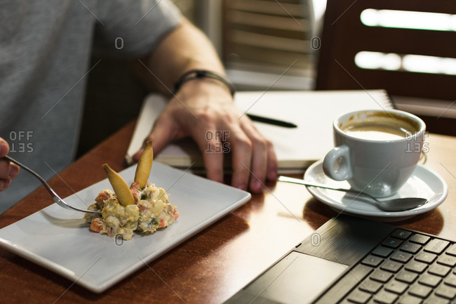 Unrecognizable man sitting at table with laptop and cup of coffee and eating tasty salad in restaurant