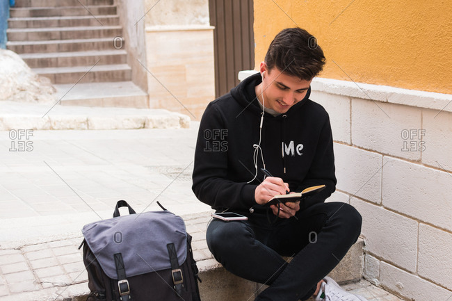 Cheerful young man in casual clothes listening to music in earphones and writing in notebook while sitting on step near backpack on city street