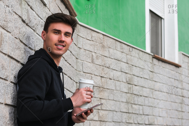 Side view of positive young male enjoying takeaway beverage and using smartphone while leaning on building wall and looking at camera on city street