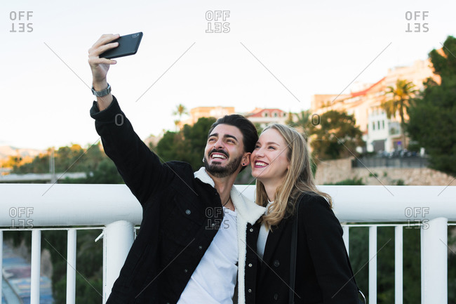 Joyful young multiracial couple in casual wear taking selfie on mobile phone while standing together on bridge with green trees and city buildings in background