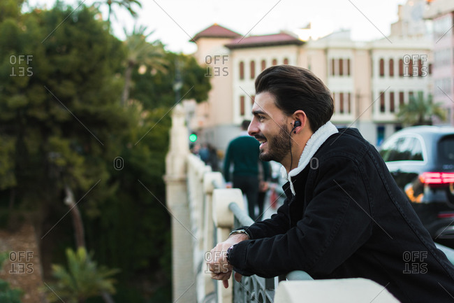 Side view of young ethnic bearded male in trendy outfit smiling and listening to music with earphones while resting on city bridge