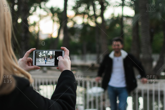 Crop anonymous woman with smartphone taking picture of boyfriend while spending time together in city park with green trees in background