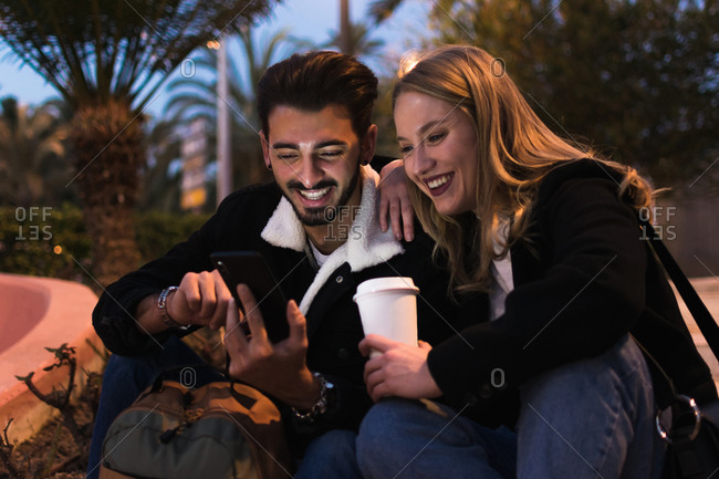 Cheerful multiethnic couple in trendy warm clothes drinking takeaway coffee and browsing smartphone while sitting together in tropical park in evening
