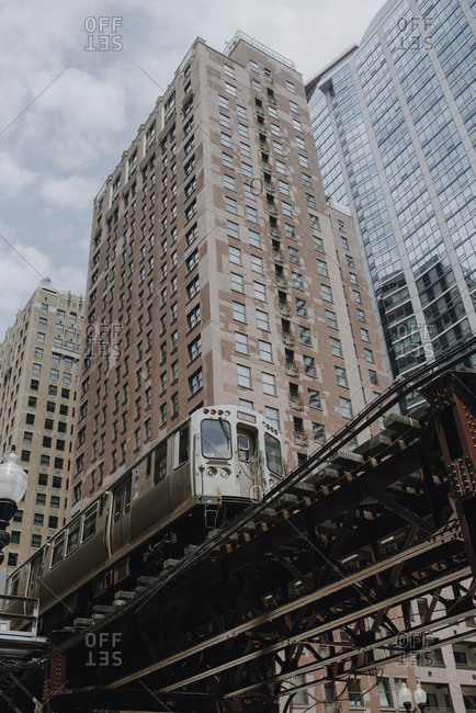 Chicago, Illinois - June 29,2029: Train on elevated road near modern buildings