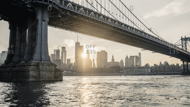 New York, New York - July 3, 029: Modern cityscape with bridge over river in evening