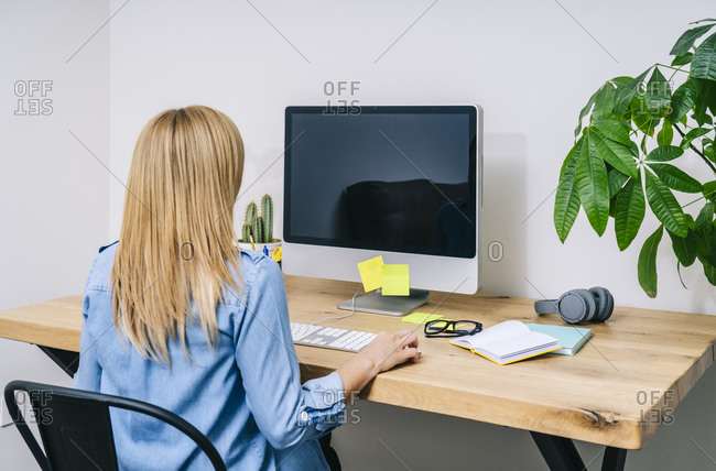 Back view o blonde caucasian woman in casual clothes sitting on wooden desk working on a computer in a modern home office