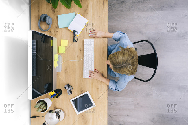 Top view of anonymous blonde caucasian woman in casual clothes sitting on wooden desk working on a computer in a modern home office