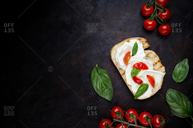 Top view of crunchy toast smeared with cream cheese and decorated with basil leaves and pieces of cherry tomatoes on black background