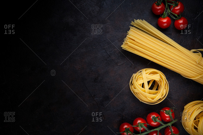 From above bunch of uncooked pasta and ripe cherry tomatoes placed on black background