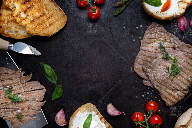 Top view of various palatable Italian dishes and cooking ingredients arranged in frame on black background