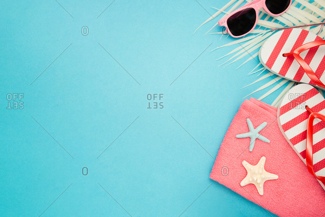 Top view composition of sunglasses and flip flops placed with beach towel on blue background with palm leaves and starfish representing summer vacation on beach