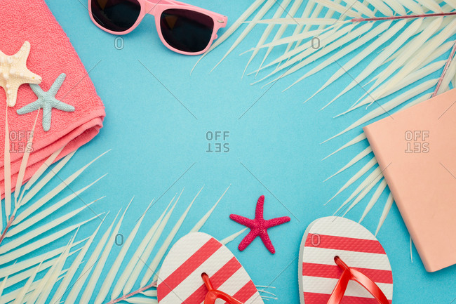 Top view composition of sunglasses and flip flops placed with beach towel and notebook on blue background with palm leaves and starfish representing summer vacation on beach