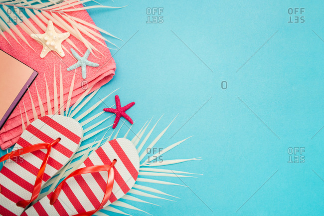 Top view composition of flip flops placed with beach towel and notebook on blue background with palm leaves and starfish representing summer vacation on beach