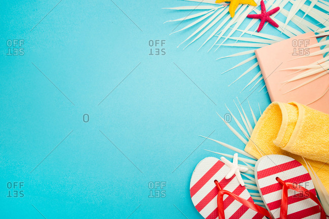 Top view of yellow beach towel placed near striped flip flops and notebook on blue background with starfish and palm leaves