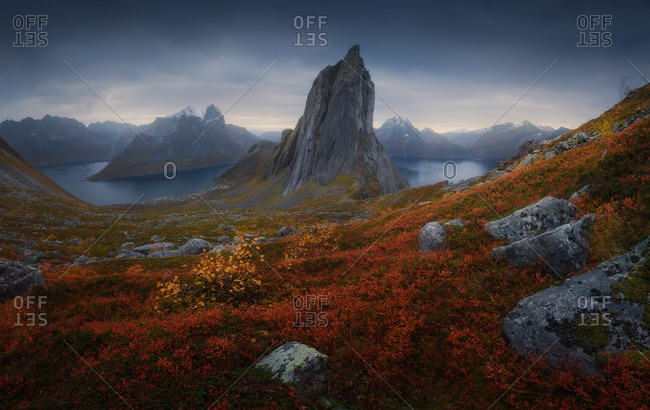 Segla mountain located in grassy valley near calm basin against dark overcast sky on island of Senja, Norway