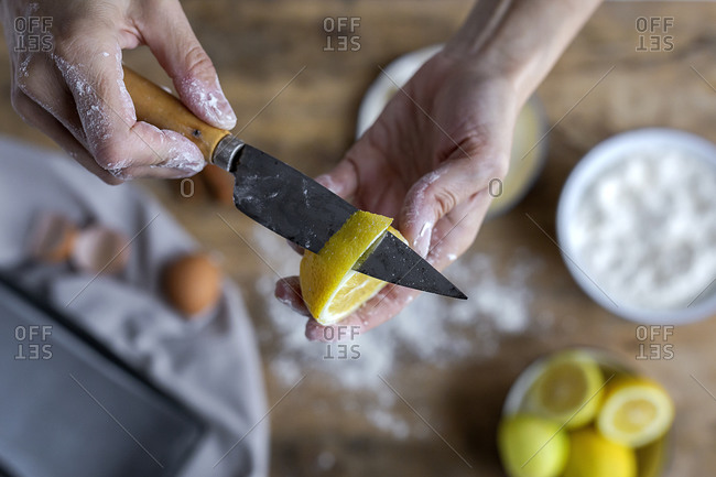From above crop hand of unrecognizable woman covered in flour peeling lemon and showing to the camera a fresh half cut lemon with knife