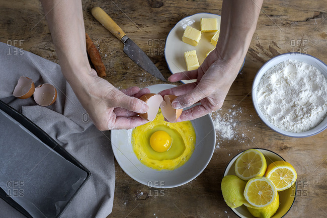 From above top view unrecognizable female breaking fresh chicken egg into bowl while cooking pastry in a wooden table with fresh ingredients