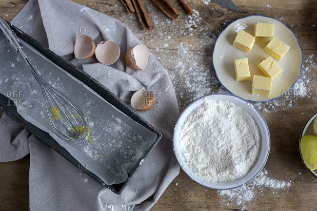 Top view of ingredients for cake recipe including bowl with flour and egg placed on dusted wooden table