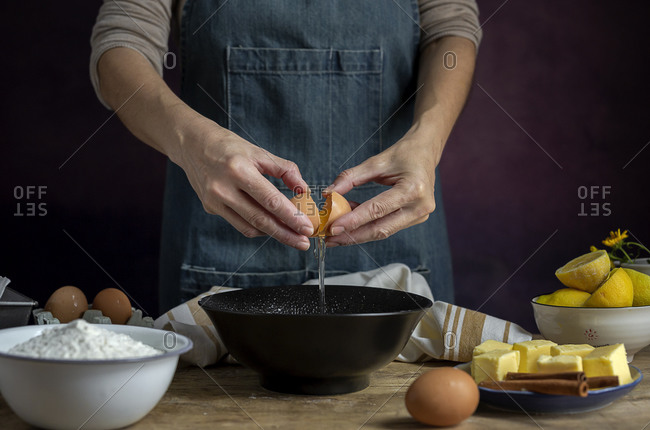 Unrecognizable female breaking fresh chicken egg into bowl while cooking pastry in a wooden table with fresh ingredients