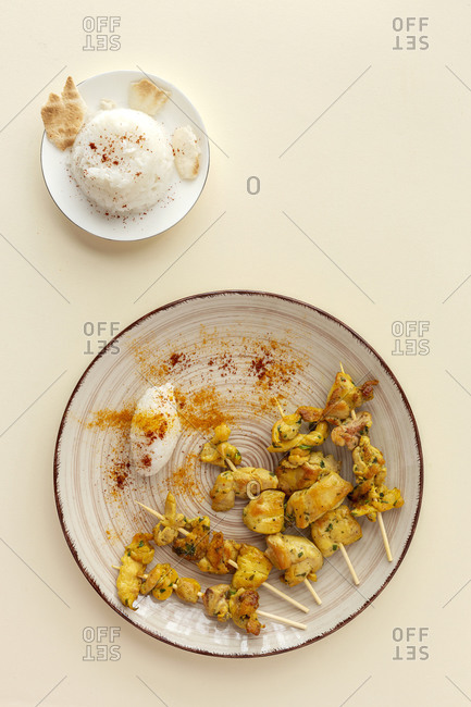 Homemade Moorish skewers with rice of meat with spices. Typical oriental food from above on beige background. Flat lay. Top view