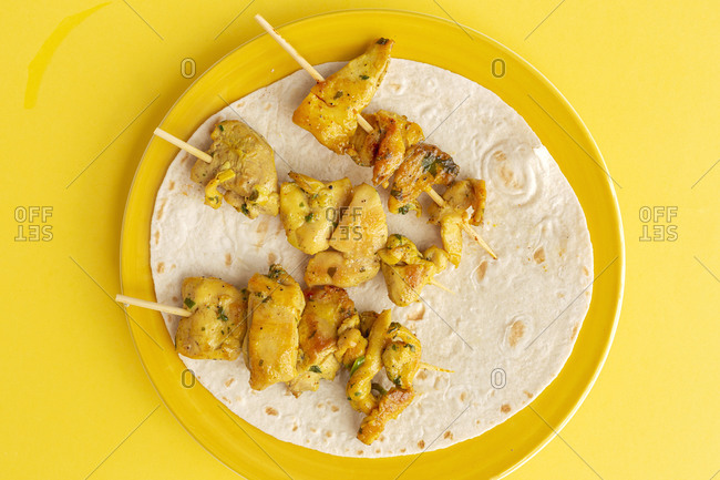 Homemade Moorish skewers with rice of meat with spices. Typical oriental food from above on yellow background. Flat lay. Top view