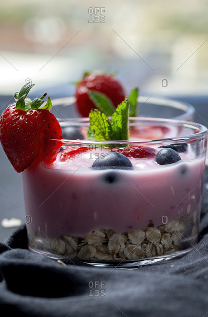 Homemade yogurt with strawberries, blueberries and cereals with dark background and sunlight. Healthy food concept. Vegan food