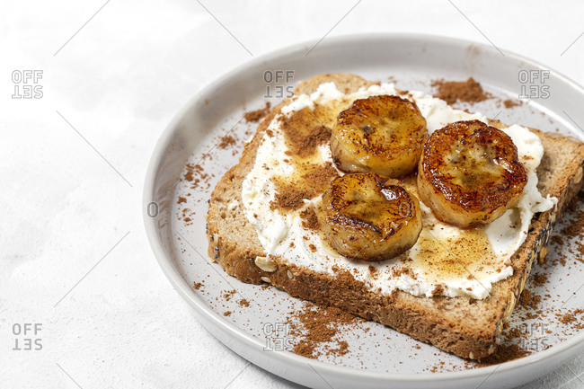 Homemade toasted bread with cream cheese, fried banana, honey and cinnamon. Vegetarian food. Healthy food concept.